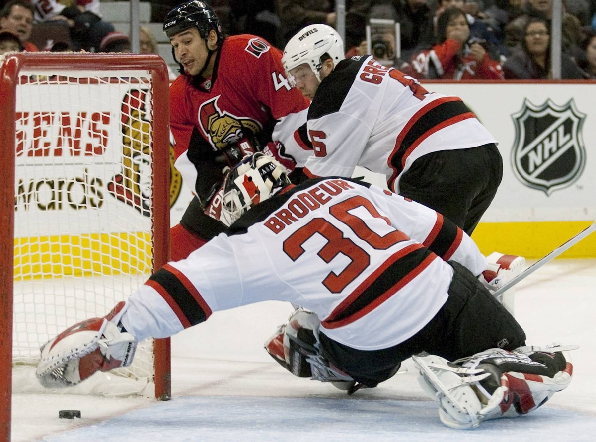 Ottawa Senators right wing Jonathan Cheechoo, 41, and New Jersey Devils defenseman Andy Greene look on as Devils goalie Martin Brodeur dives for the puck as it crosses the goal line during second period NHL action in Ottawa Saturday November 7, 2009. The goal was awarded to Ottawa Senators defenseman Brian Lee. THE CANADIAN PRESS/Pawel Dwulit