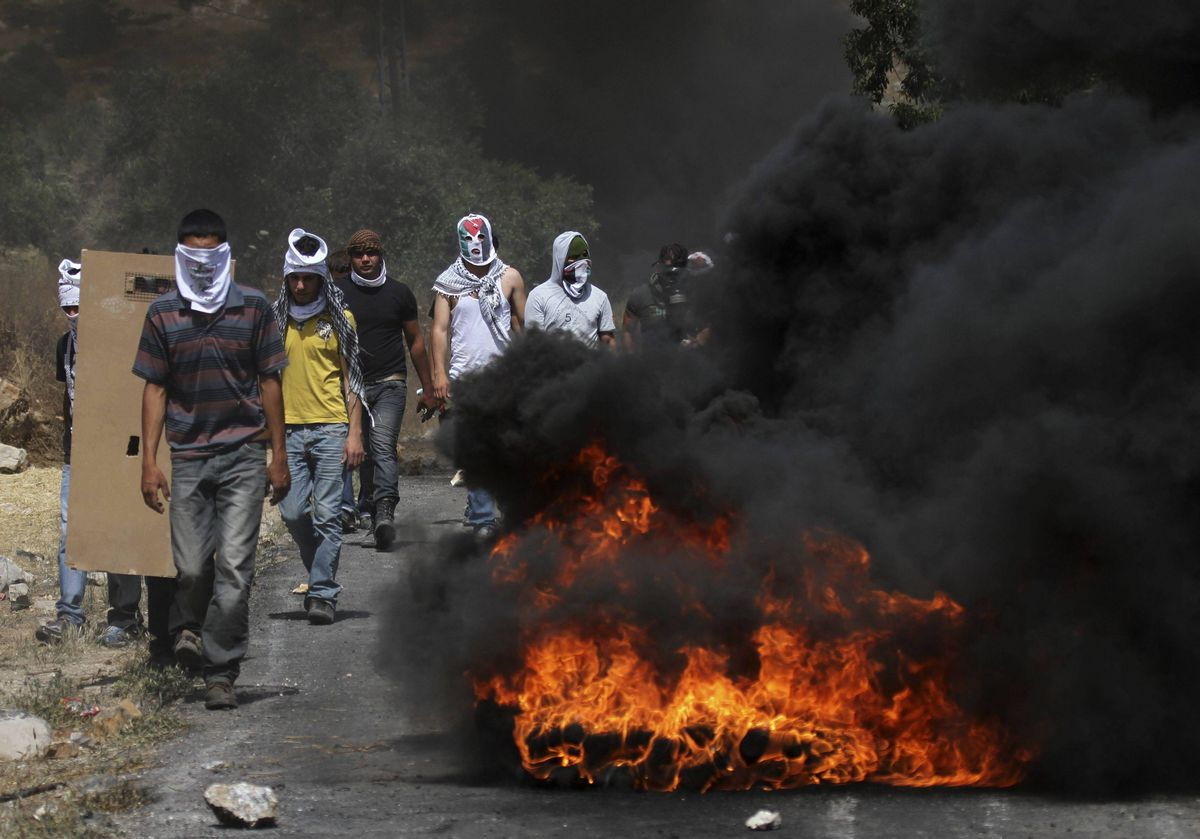 Palestinian protesters walk near tyres they set ablaze during clashes with Israeli soldiers at a demonstration in the village of Kfar Qaddum against the nearby Jewish settlement of Qadomem, near the West Bank City of Nablus.