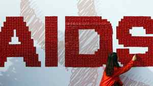 A woman attaches a condom on the board during an AIDS awareness campaign to increase awareness of the sexually-transmitted fatal disease in Seoul, South Korea, Thursday, Dec. 1, 2011.