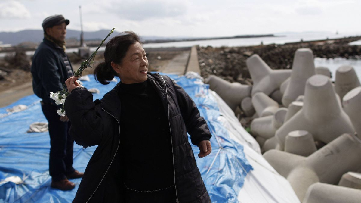 Shizuko Ohashi throws flowers toward the sea to mourn her friends who died in the 2011 quake, as friend Toshio Ishikawa looks on in Ishinomaki, Miyagi prefecture, on Sunday.