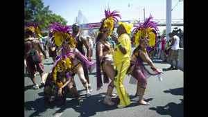 Revelers join costumed members of the Caribbean Carnival parade.