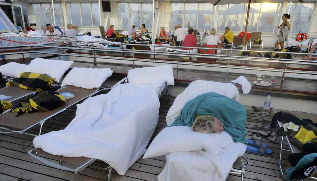 In this image taken on Tuesday, Feb. 28, 2012 by a passenger of the Costa Allegra cruise ship, a passenger sleeps on the deck of the ship. A disabled cruise ship carrying more than 1,000 people docked in the island nation of the Seychelles Thursday after three days at sea without power since a fire broke out in the generator room on Monday.