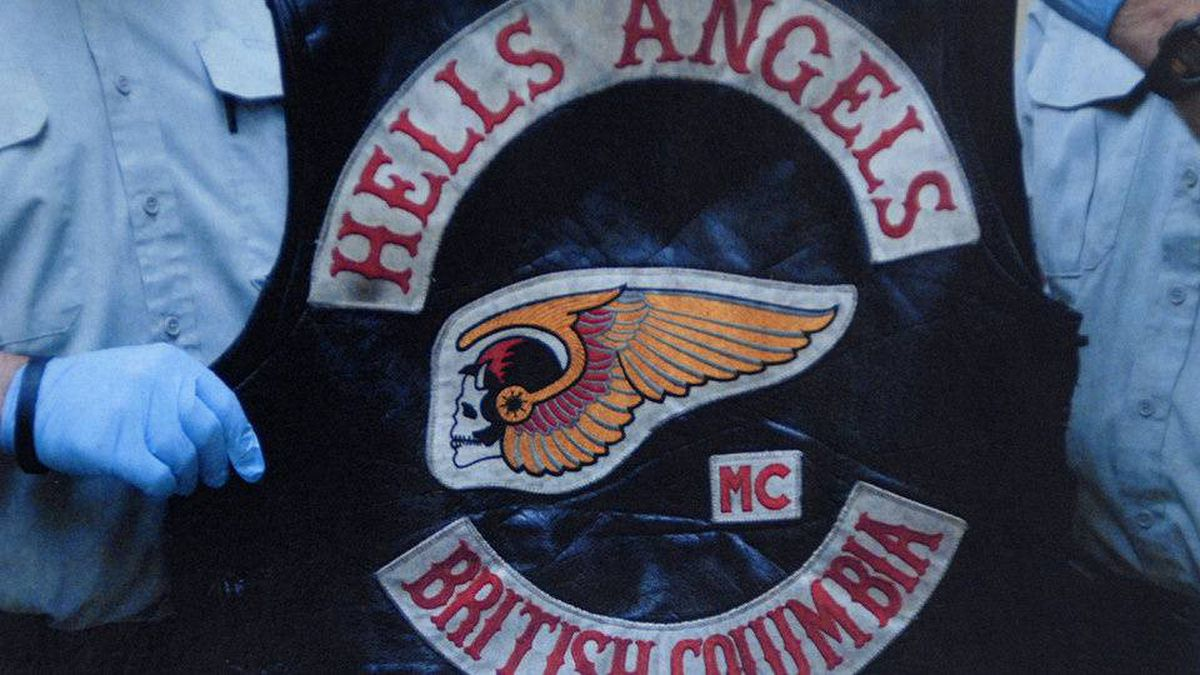 A Hells Angel vest being held by RCMP officers.