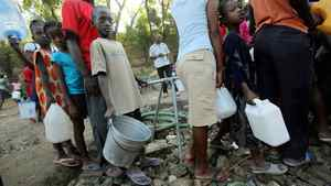 Earthquake survivors in Port-au-Prince wait in line to collect water this week. Aid groups in Canaday say they've been warned by the Conservatives not to weigh in on policy.