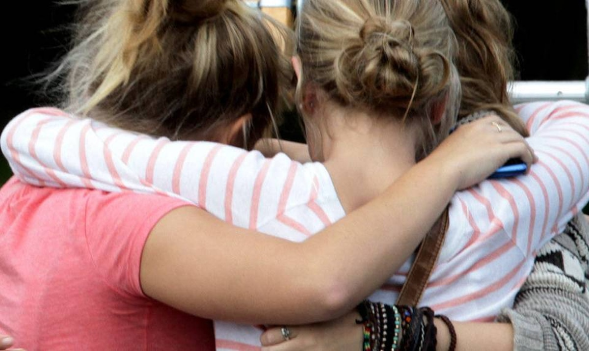 Students embrace outside Burnsview Secondary School as they gather for a meeting to be updated on the death of 15-year-old Laura Szendrei, who attended the school, in Delta, B.C., on Monday September 27, 2010.