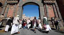 Yemeni people walk in front of the main entrance of Old Sanaa city on Jan. 7, 2010.