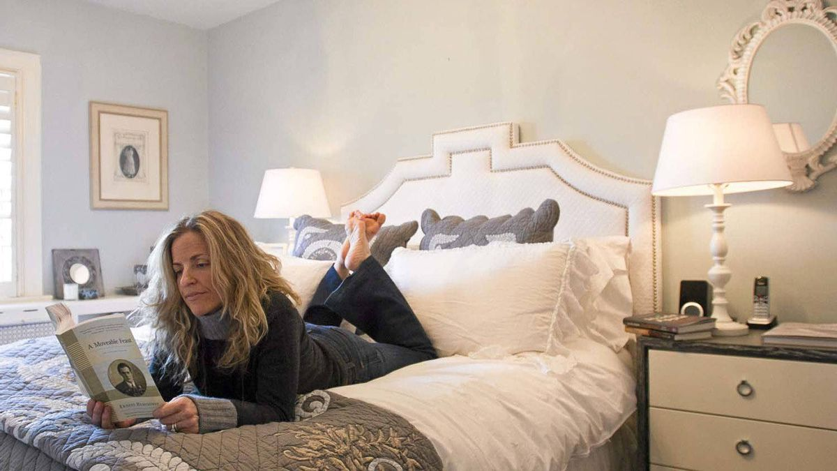 Author Joanna Goodman reads in her bedroom at her home in Toronto.