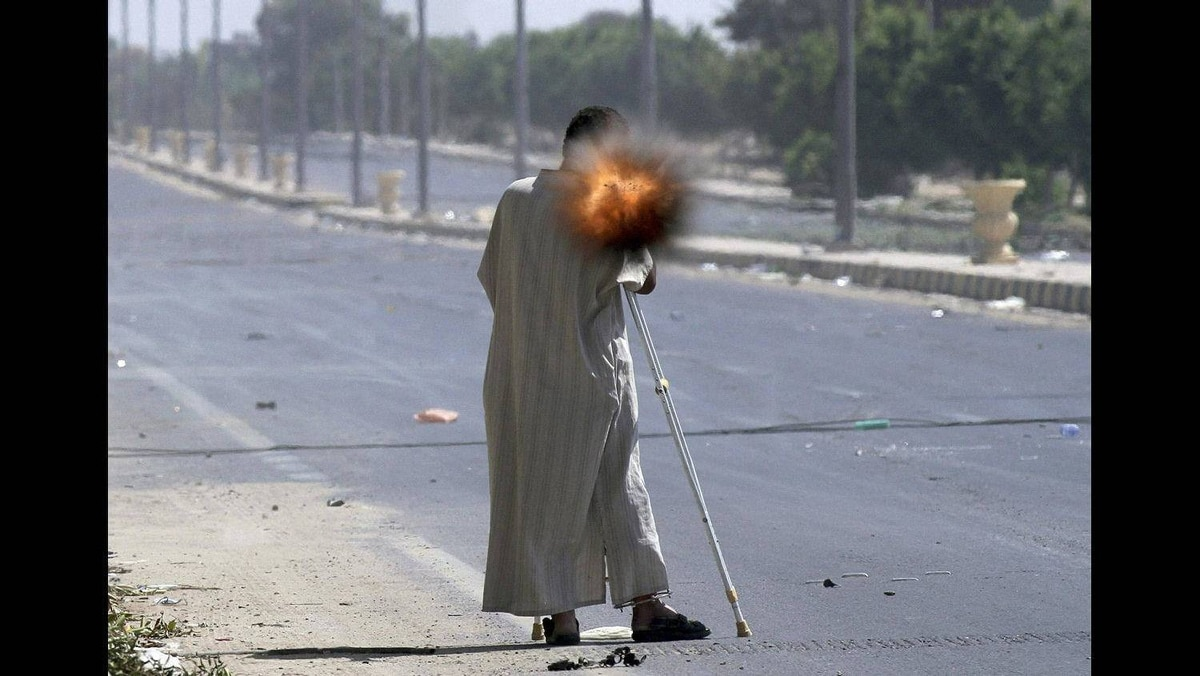 A rebel on crutches fires a rocket propelled grenade while fighting on the front line in Sirte September 24, 2011.