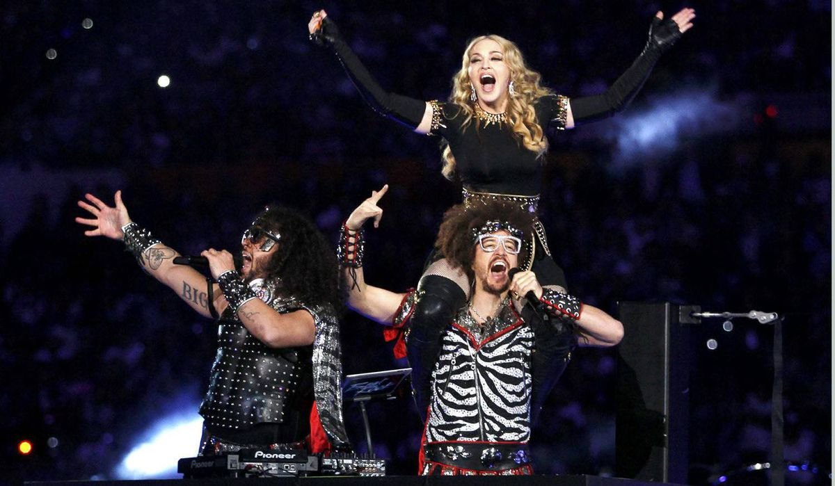 Madonna performs during the halftime show with Redfoo aka Stefan Kendal Gordy (R) and SkyBlu aka Skyler Husten Gordy of LMFAO in the NFL Super Bowl XLVI halftime show.