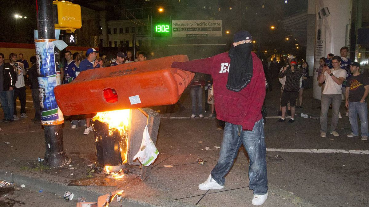 A man tries to burn a a plastic barricade during the riot in Vancouver June 15, 2011.