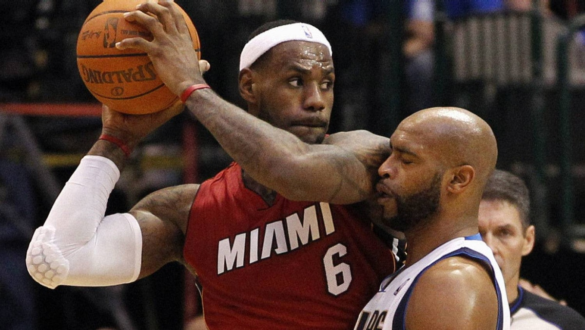 Miami Heat forward LeBron James (L) controls the ball as he is defended by Dallas Mavericks guard Vince Carter during the second half of their NBA basketball game in Dallas, Texas December 25, 2011. The Heat won 97-69. REUTERS/Mike Stone