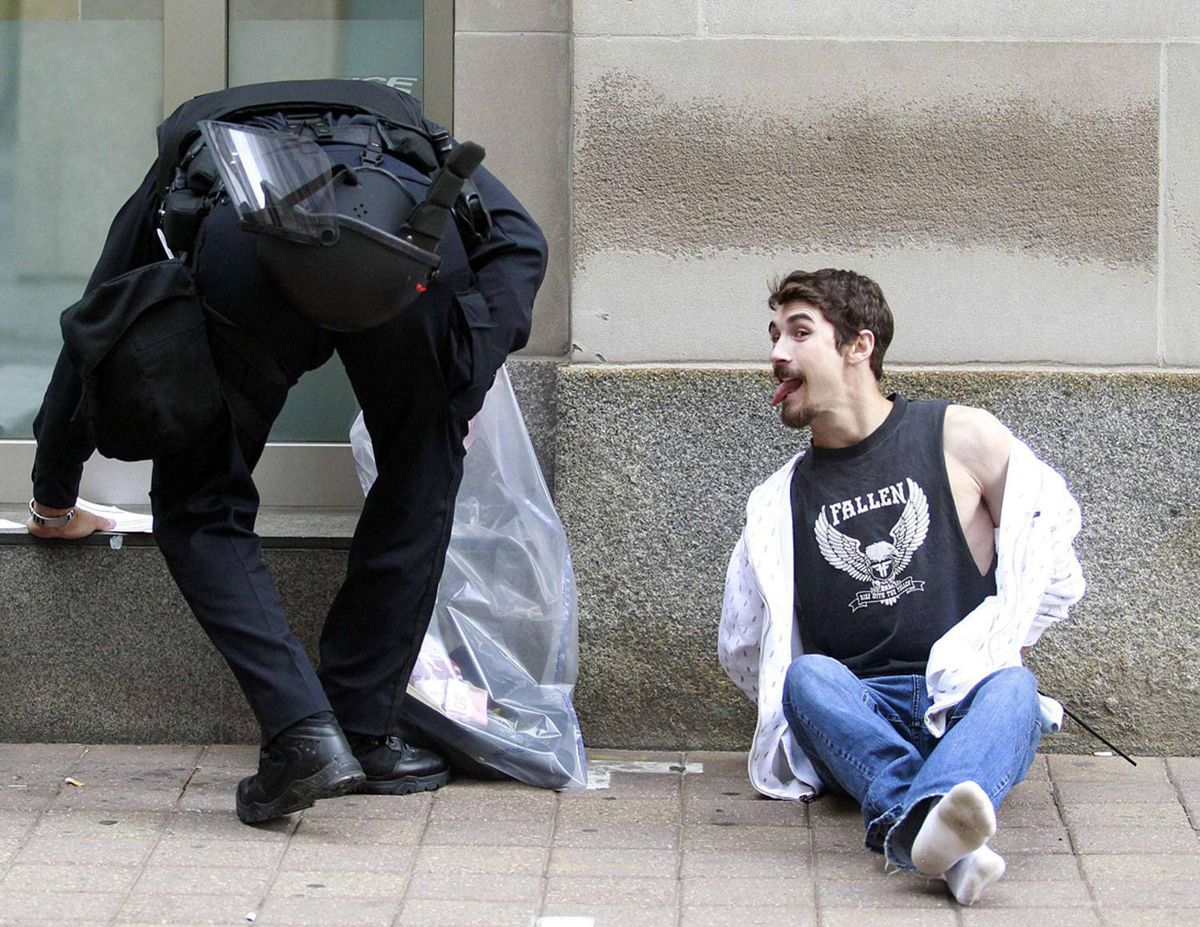 A man sticks his tongue out at a police officer after being arrested during a protest at the G20 summit in downtown Toronto, June 27, 2010.