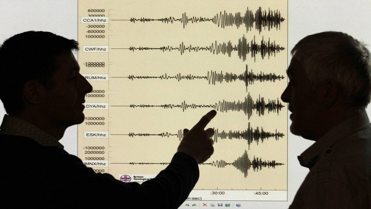 Seismologists examine the graph of a massive arthquake in Japan at the British Geological Survey office in Edinburgh on March 11, 2011.