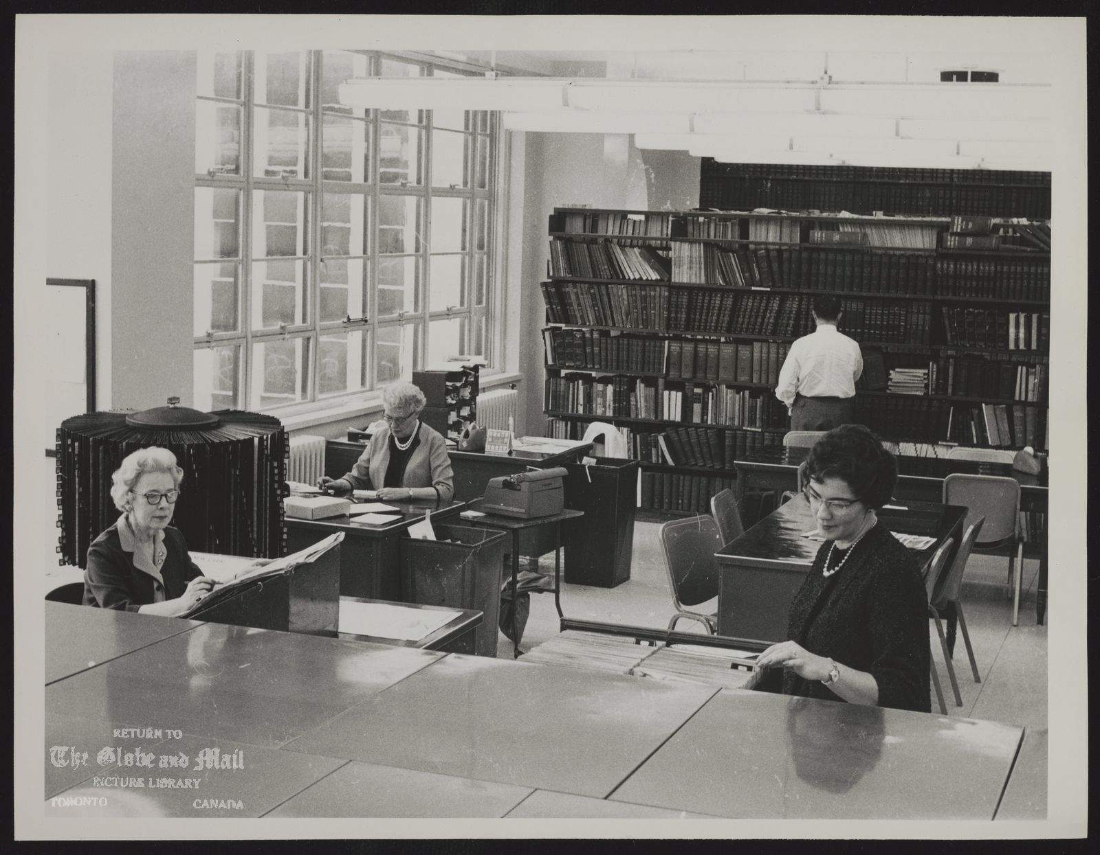 The notes transcribed from the back of this photograph are as follows: [Globe and Mail staff members at work in the editorial library of the William H. Wright building, home of The Globe and Mail in downtown Toronto. Library staff, left to right: Evelyn Haffey, Kay Chalmer, David Rhydwen at rear with back to camera, Cathie Cunningham. Photo by John Boyd / The Globe and Mai