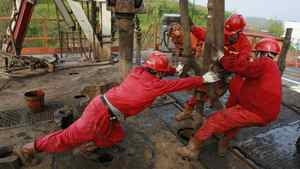 Labourers work at a well head in a PetroChina oil field in Tongnan, southwest China's Sichuan province.