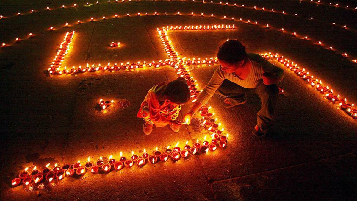 Children light lamps in the shape of Swastika, on the eve of Hindu festival of Diwali, in the northern city of Chandigarh, November 11, 2004. According to Hindu mythology, the swastika is the sign of prosperity. People decorate their homes with lights during the biggest Hindu festival of lights.