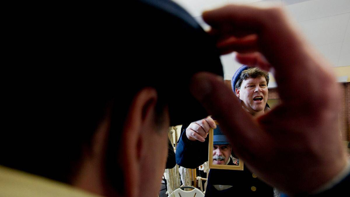 Glendon Hovey holds a mirror for a customer trying on a gentleman's hat. Mr. Hovey's company, Sew Historic, provides historical garments and accoutrements for men.