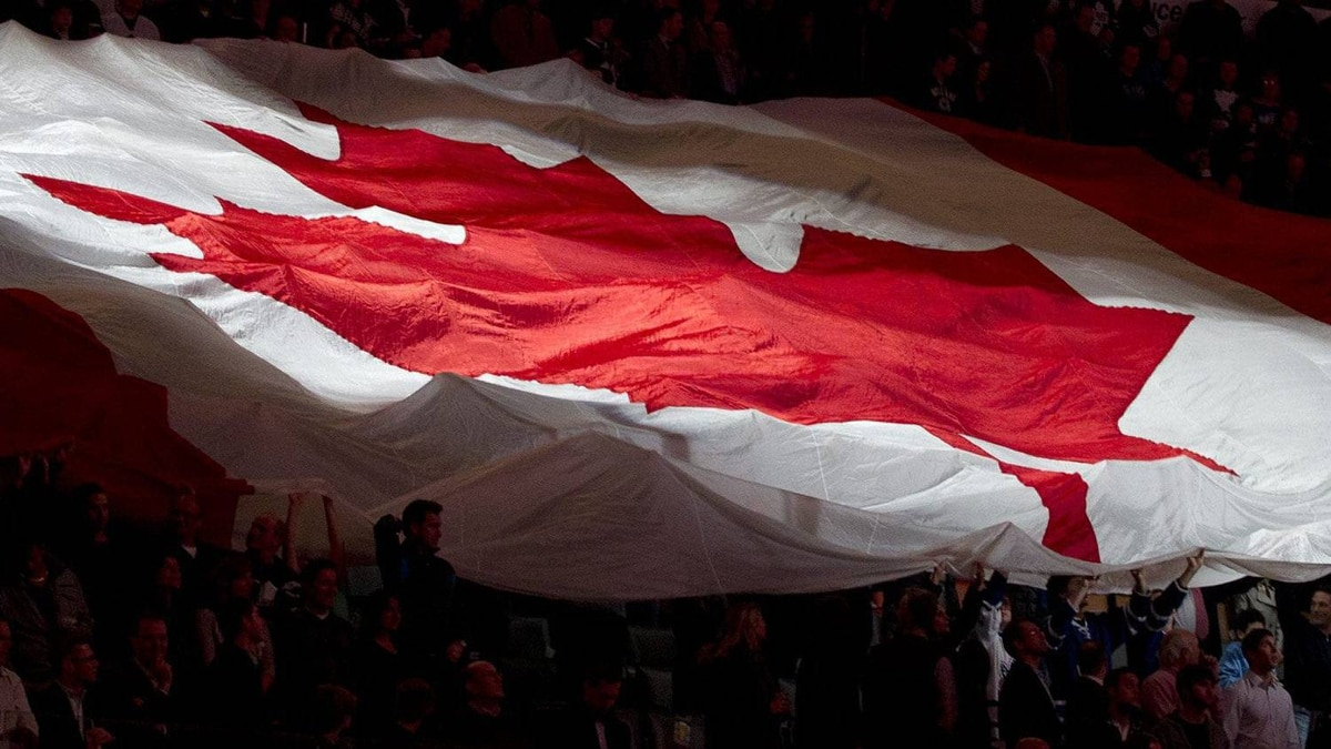 A giant Canadian flag is passed over the crowd during the singing of the national anthems prior to NHL action between the Toronto Maple Leafs and New Jersey Devils in Toronto on Tuesday December 6, 2011. THE CANADIAN PRESS/Frank Gunn