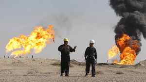 Iraqi workers walk in South Rumaila oil field, in southern Iraq, December 2, 2009.