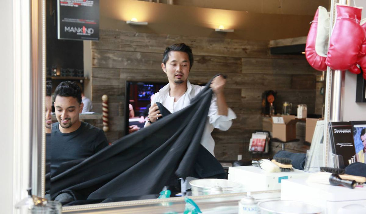 A happy customer smiles as lead stylist and co-owner of Mankind Grooming Studio, Jason Culala, removes the salon robe