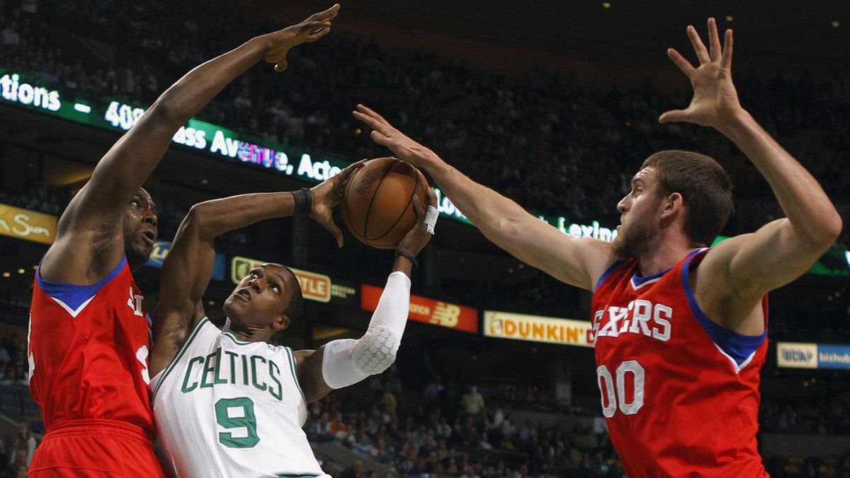 Boston Celtics guard Rajon Rondo (C) drives to the basket between Philadelphia 76ers forwards Elton Brand (L) and Spencer Hawes (R) during the first quarter of Game 5 of their NBA Eastern Conference playoff series in Boston, Massachusetts May 21, 2012. REUTERS/Brian Snyder