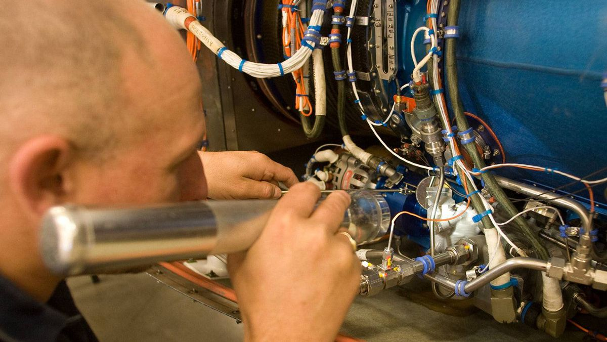 Stewart Clarke uses a small mirror and flashlight to inspect components inside the D-JET's engine.