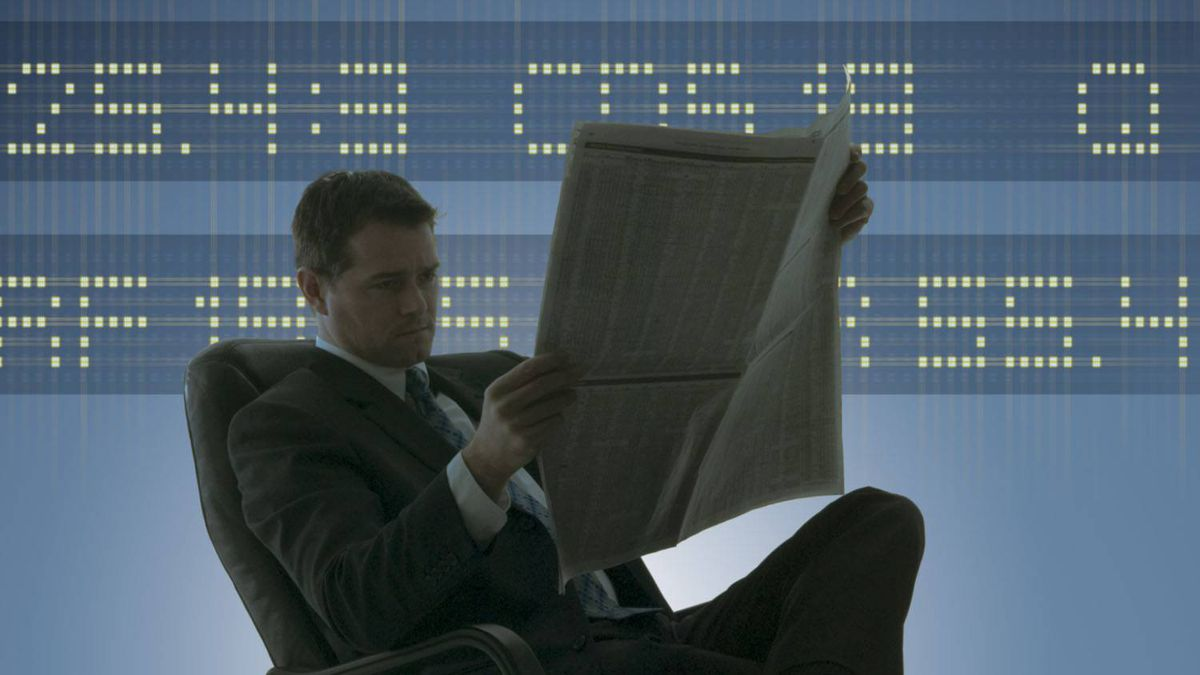 Businessman reading newspaper and stock ticker