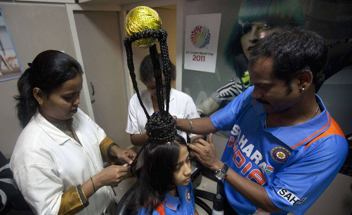 Hairdressers shape the hair of cricket fan Rajna Pandit, 22, to resemble the Cricket World Cup trophy in Mumbai February 17, 2011. The Cricket World Cup is jointly hosted by India, Sri Lanka and Bangladesh and takes place from February 19 to April 2.