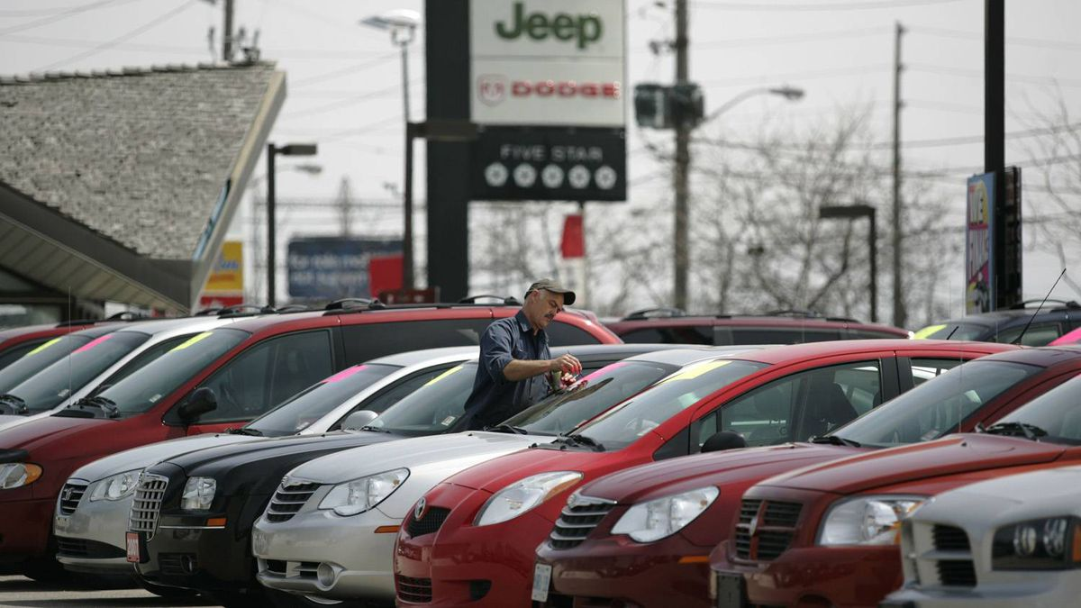 A worker paints prices on cars at a Dodge Chrysler dealership in Toronto