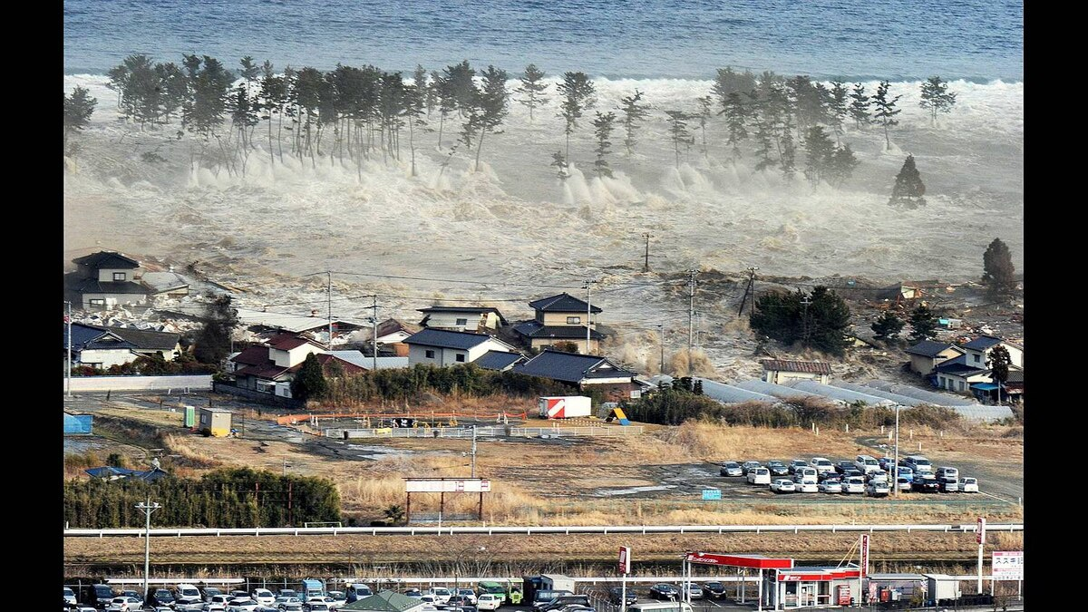 A massive tsunami sweeps in to engulf a residential area after a powerful earthquake in Natori