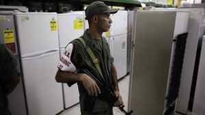 A member of the National Guard stands guard during a inspection of prices at a store in La Guaira outside Caracas