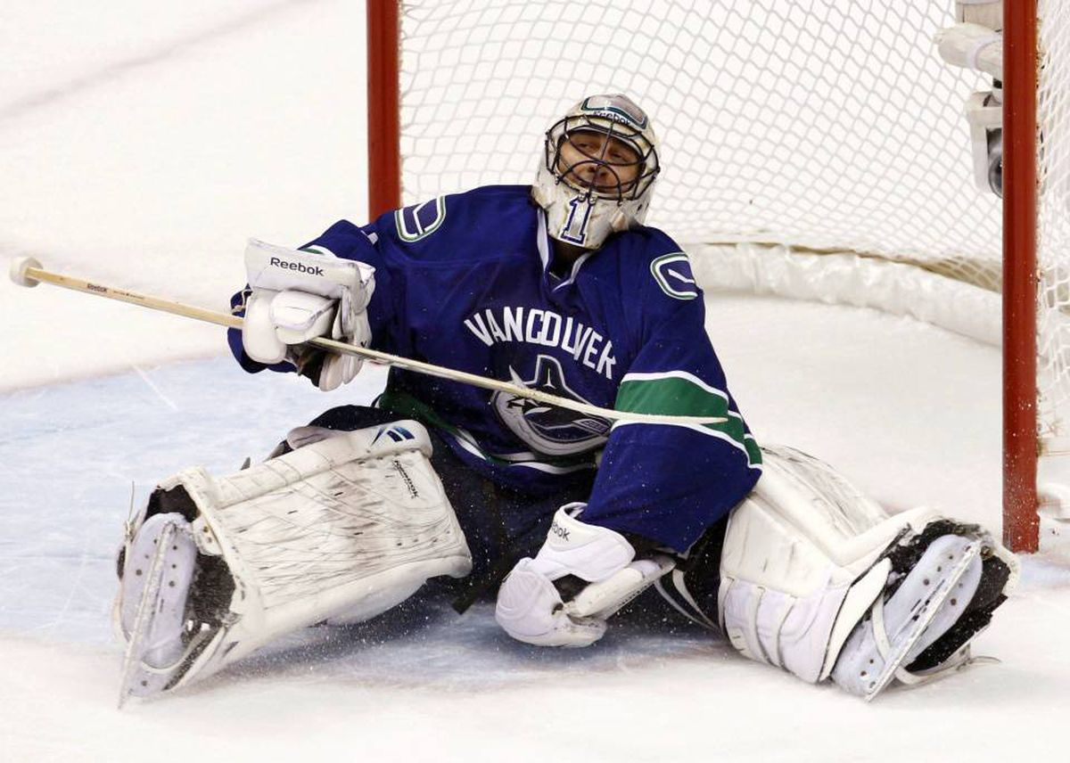 Vancouver Canucks goalie Roberto Luongo sits on the ice with the puck in his glove after making a break-away save on Chicago Blackhawks center Patrick Sharp in the first period during Game 6 of their NHL Western Conference semi-final hockey game in Vancouver, British Columbia May 11, 2010.