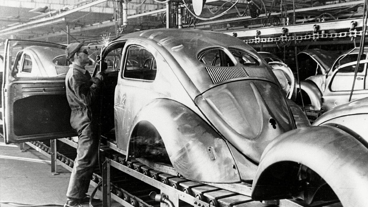 A worker welds a body component at the VW factory in 1947. At this point, the Beetle used a split rear window, which increased structural rigidity and reduced costs by allowing smaller glass panes.