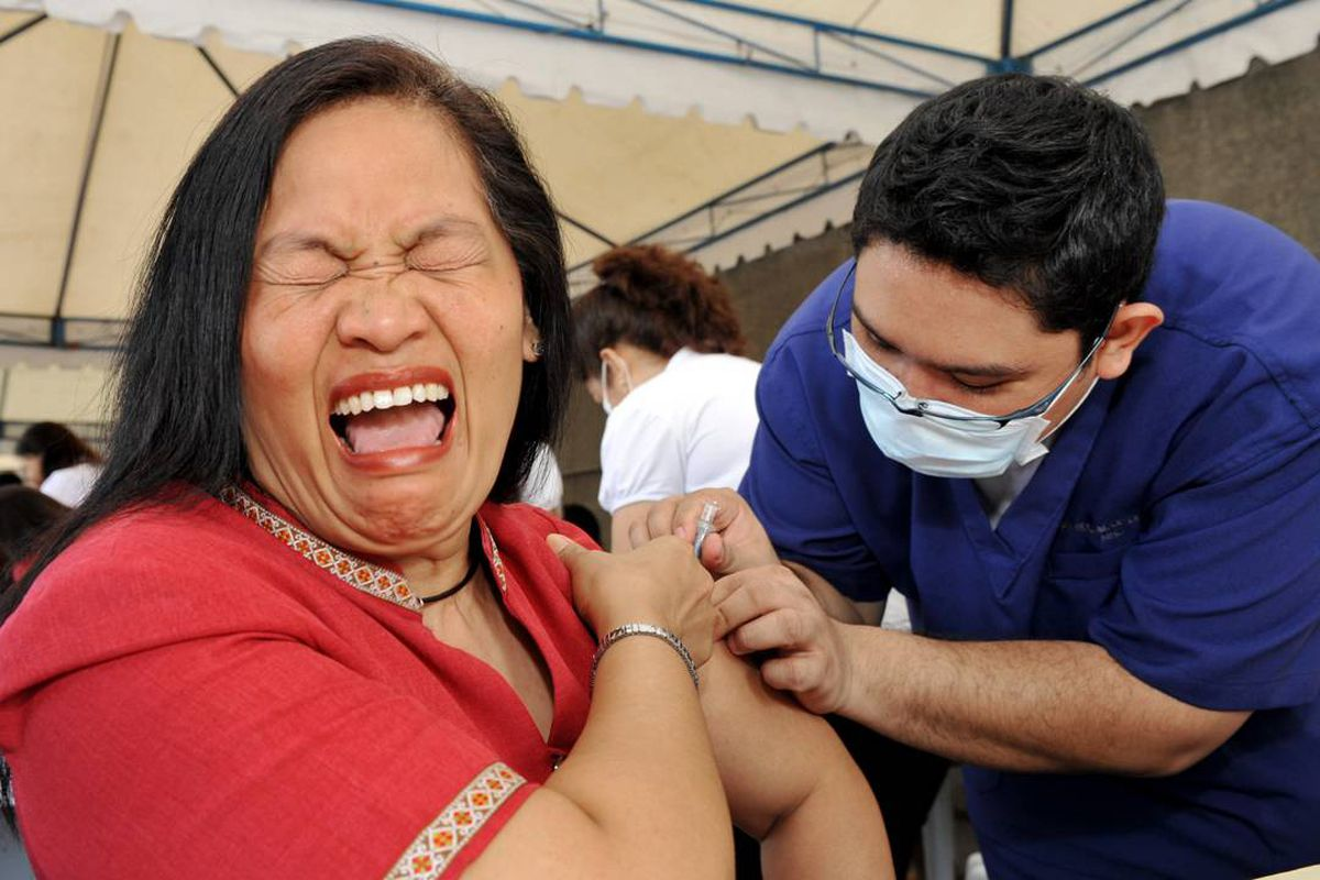 A city government employee grimaces as she receives a vaccination against ordinary seasonal flu in the financial district of Manila. Ted Aljibe/AFP/Getty Images