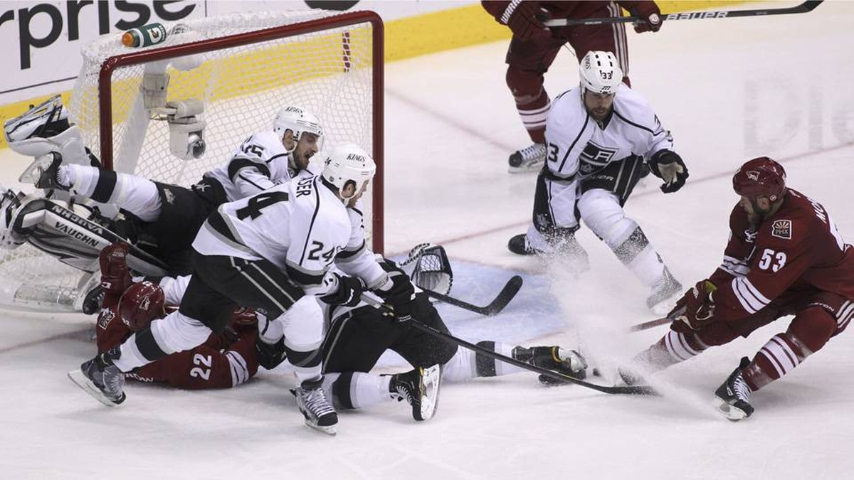 Phoenix Coyotes defenseman Derek Morris (R) is stopped from scoring by Los Angeles Kings defenseman Willie Mitchell (33), Colin Fraser (24) and Brad Richardson (15) as they help out goalie Jonathan Quick in the 2nd period during Game 1 of the NHL Western Conference hockey finals.