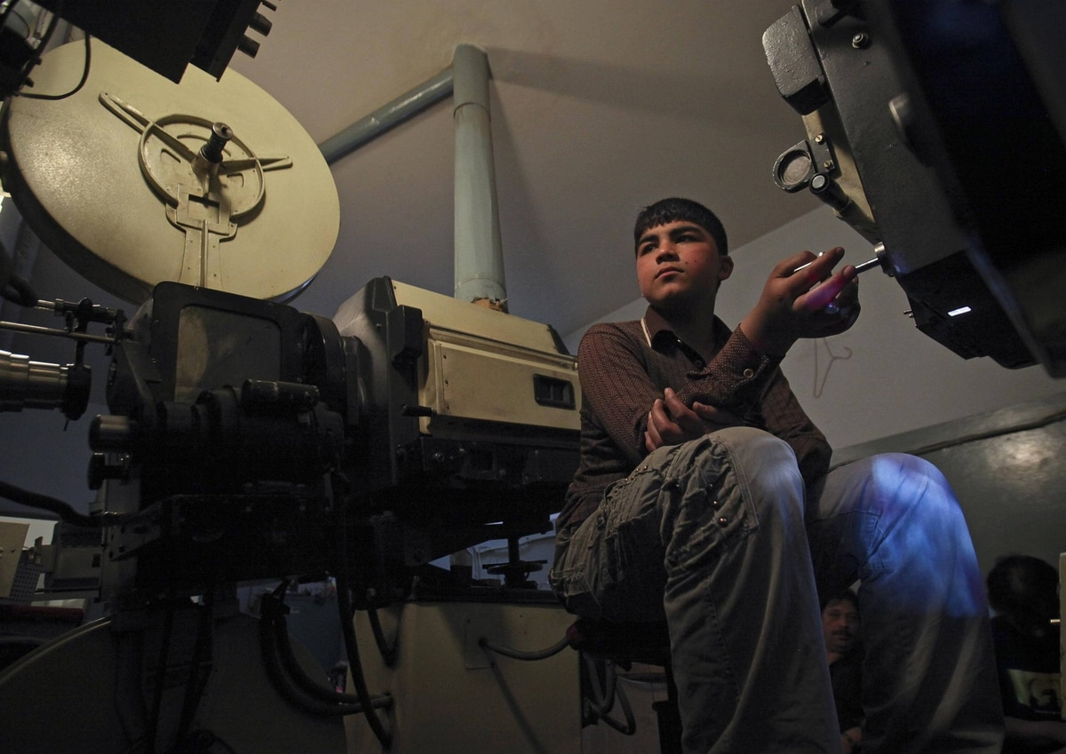 Ahmad Wali, a 15-year-old projectionist, works inside the projection room at Pamir Cinema in Kabul.