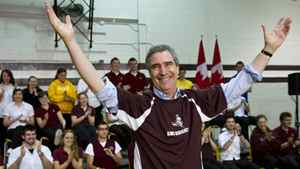 Liberal Leader Michael Ignatieff salutes the crowd after slipping on a team jersey during a town hall meeting with high school students in Sault Ste Marie, Ont.
