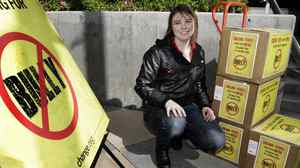 Katy Butler, a high-school student from Michigan and a onetime target of bullying, poses with boxes containing more than 210,000 petition signatures that she is delivering to the Los Angeles office of the Motion Picture Association of America to urge the MPAA to lower the rating of the documentary Bully from R to PG-13, in Los Angeles, March 7, 2012.