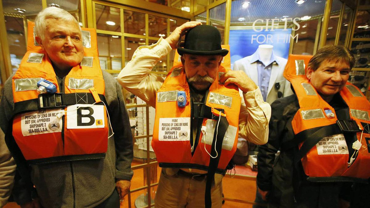John Philip (C) of South Coast, New South Wales, Australia adjusts his period bowler hat while donning a life jacket, during a drill on board the Titanic Memorial Cruise in Southampton, England April 8, 2012.