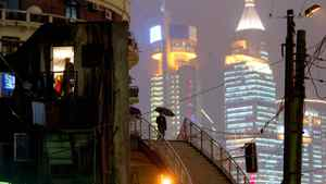 A Chinese woman (with umbrella) walks in between the new and old districts of Shanghai October 31, 2002.