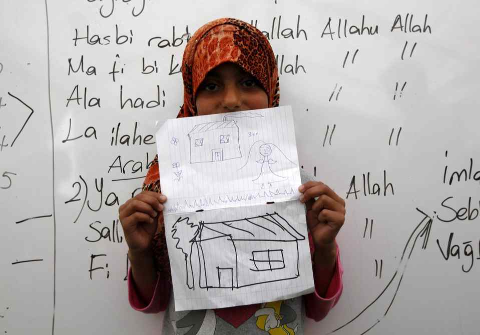 Rozi Yesuf, 10, a Syrian refugee, shows a drawing of her dream home during a class at a school for refugee children at Boynuyogun refugee camp in Hatay province near the Turkish-Syrian border.