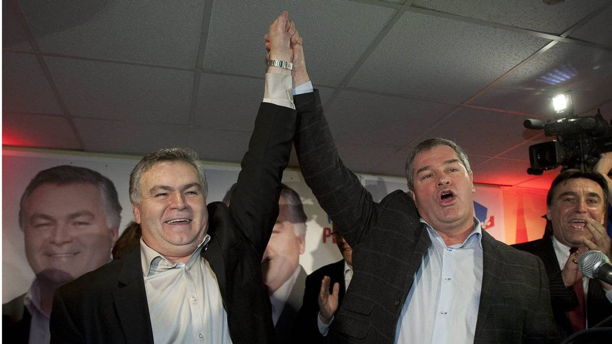 Quebec Liberal candidate Damien Arsenault, left, gets his hand raised in victory by Health Minister Yves Bolduc after winning a by-election in the riding of Bonaventure.