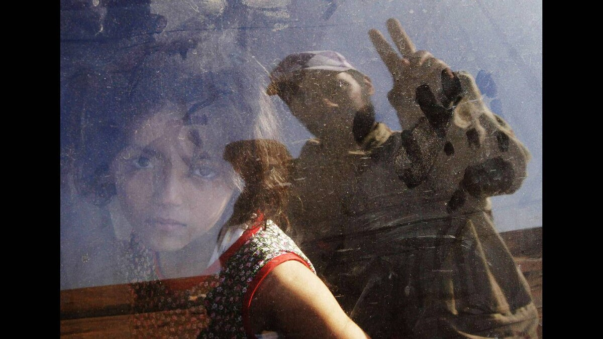 A girl fleeing the unrest in Bani Walid with her family looks on as an anti-Gaddafi fighter flashing a victory sign is reflected in a car window on the outskirts of Bani Walid September 14, 2011.