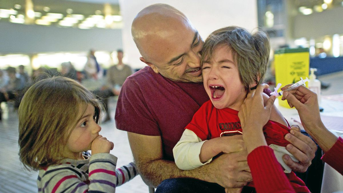 Juan Mosquera holds his son Jasper, 4, as he receives a flu shot with little sister Hazel, 3, looking on at city hall in Toronto, Ont. Jan. 11, 2011.