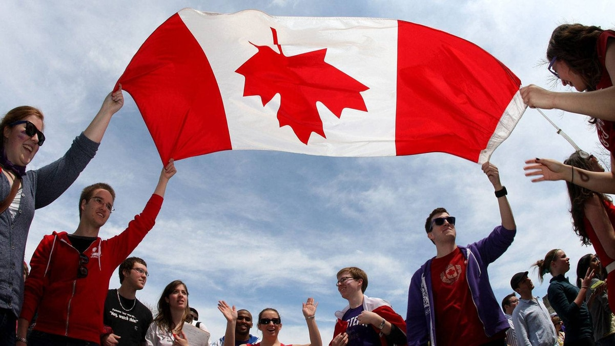 A Canadian flag is floated above their heads by some of the crowd during a voter rally in London, Ont., Saturday, April 30, 2011.