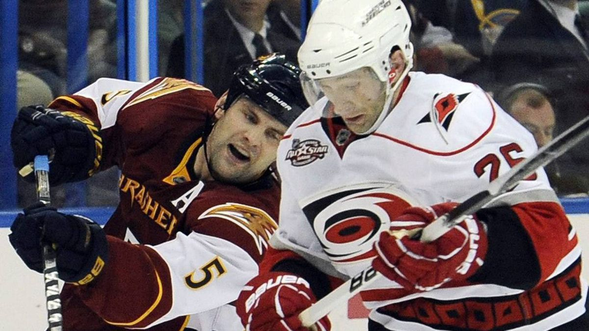 Carolina Hurricanes right wing Erik Cole (26) and Atlanta Thrashers defenseman Mark Stuart (5) battle for the puck during the second period of an NHL hockey game, Friday, April 8, 2011, in Atlanta. (AP Photo/John Amis)