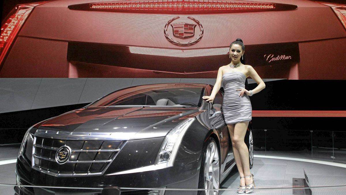 A model stands next to a Cadillac ELR at Auto China 2012.