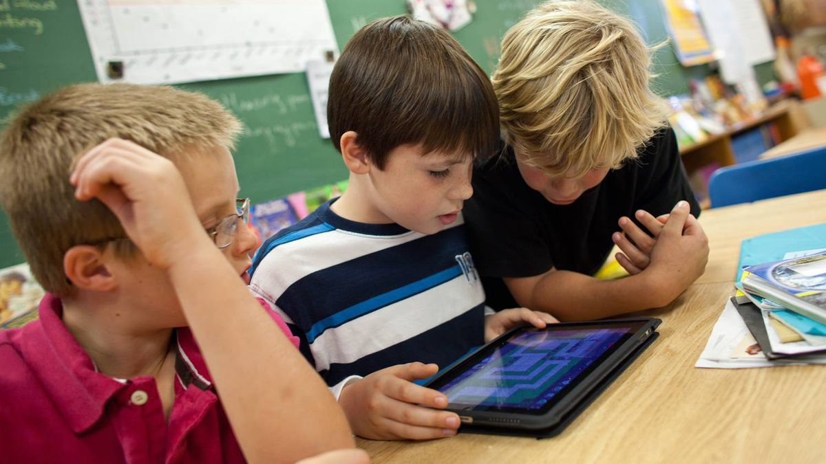 Nicklaus O' Rourke, left, Noah Dobbiestamos and Owen Hakker play with an iPad.