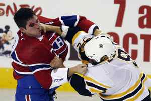 Montreal Canadiens Gregory Stewart, left, fights with Boston Bruin Guillaume Lefebvre during the first period of their NHL preseason hockey action in Montreal, September 24, 2009.