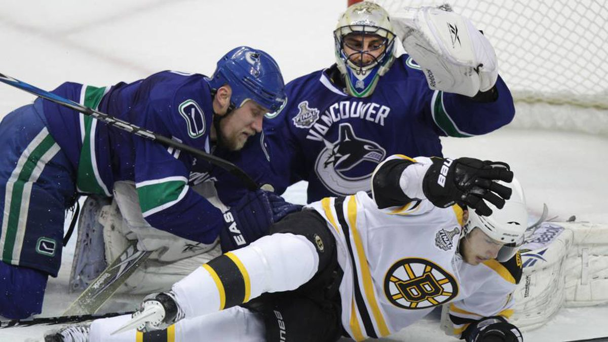 Boston Bruins forward Tyler Seguin gets pushed down by Vancouver Canucks defenceman Sami Salo as goalie Roberto Luongo looks on in the first period.
